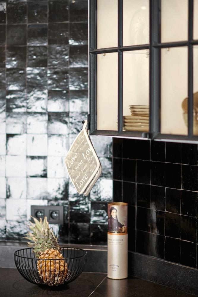 Foto van keukenaanrecht in zwarte stijl met donkere tegels, met fruit op het aanrecht