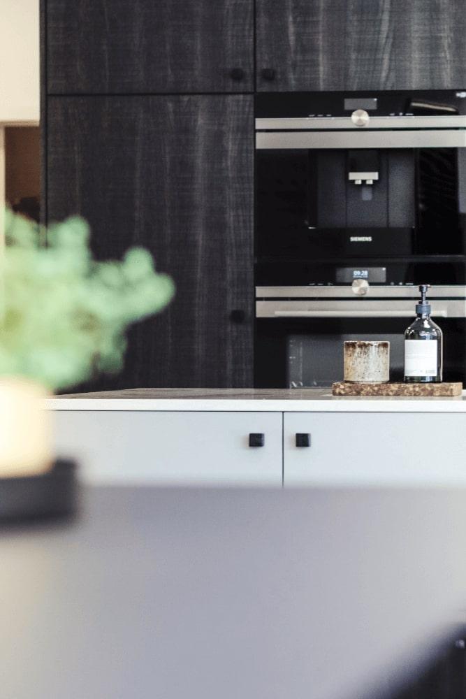 Moderne keuken in zwartwitte afwerking, met zwarte kasten