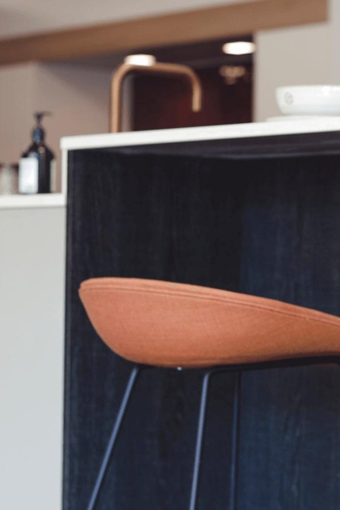 Barkruk in cognackleur onder een keukeneiland, in de achtegrond een moderne keukenkraan - ACK Keukens