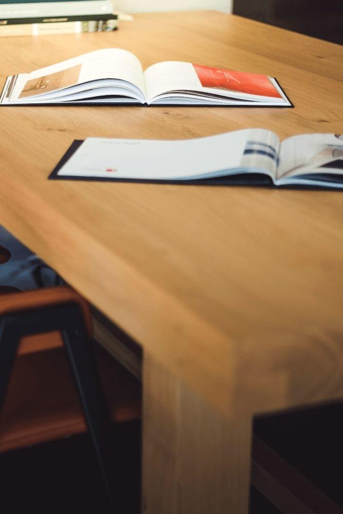 Brochures om een keuken te kiezen liggen op een houten keukentafel - ACK Keukens