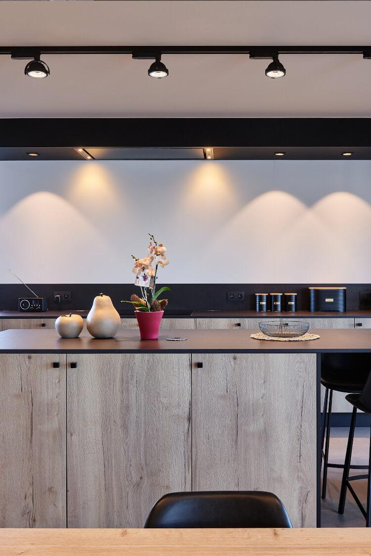 Modern keukeneiland met houten afwerking, bloemen op tafel