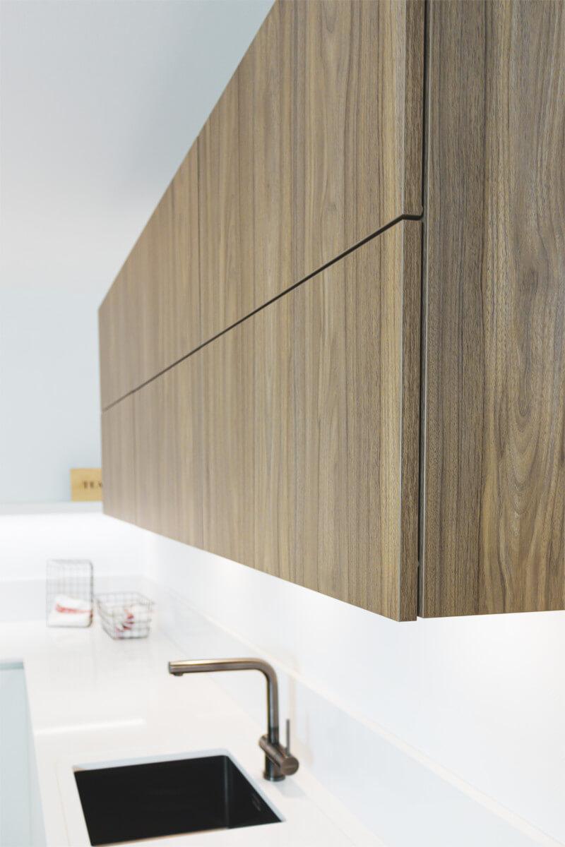 Moderne keuken met greeploze keukenkasten in laminaat notenhout - ACK Keukens